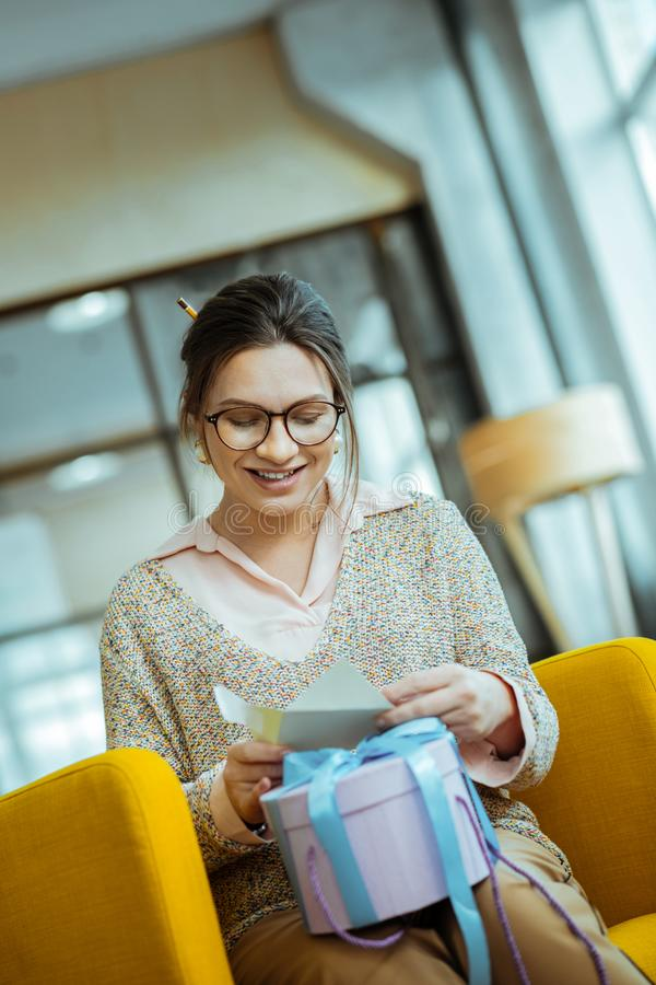Businesswoman wearing glasses receiving present in office stock image
