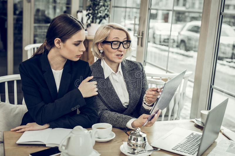 Businesswoman wearing glasses speaking with her young employee royalty free stock photography