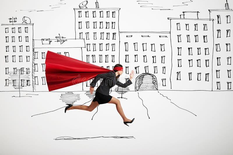 Businesswoman wearing like superhero very fast running in drawed street. Serious businesswoman wearing like superhero very fast running in drawn street stock image