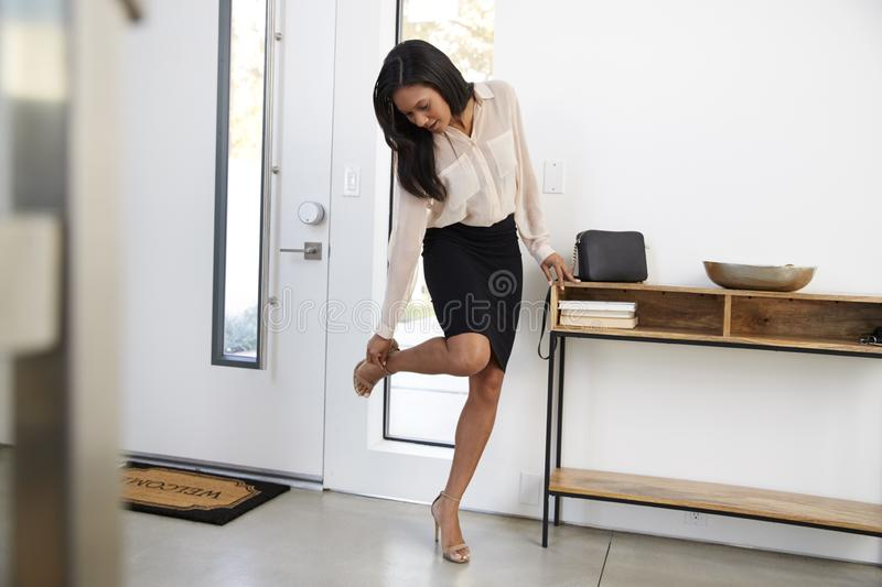 Businesswoman Wearing Suit Returning Home From Work And Taking Off Shoes royalty free stock photos