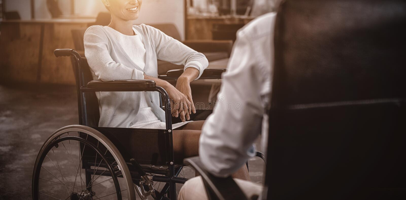Businesswoman in wheelchair talking with colleague in office stock images