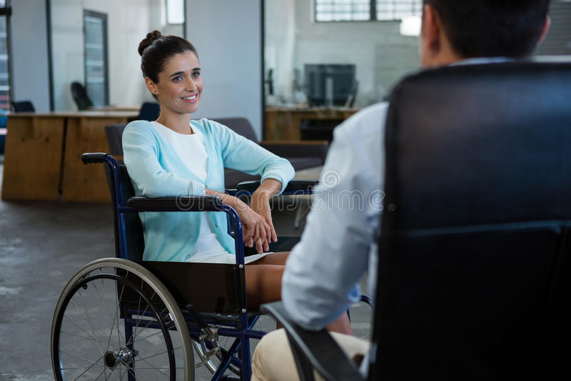 Businesswoman in wheelchair talking with colleague in office stock image