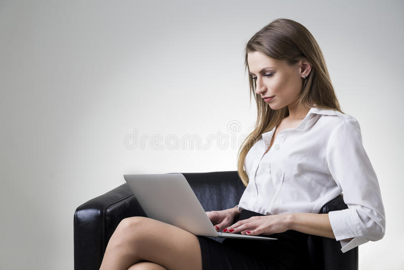 Businesswoman in a white blouse sitting in a leather armchair with her laptop. Side view of a beautiful businesswoman in a white blouse sitting in a leather stock photos