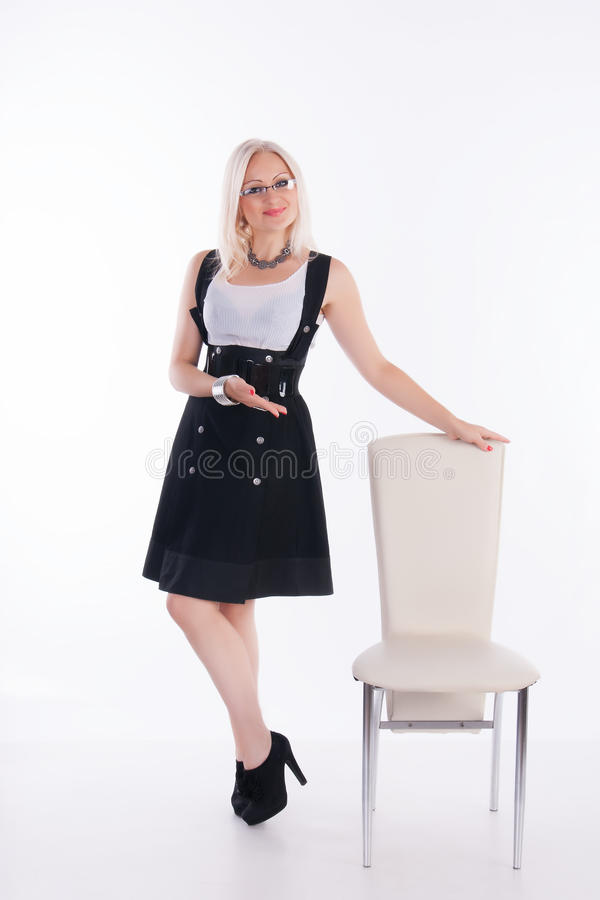 Businesswoman. The woman invites you to sit down on a chair at the white background stock photo