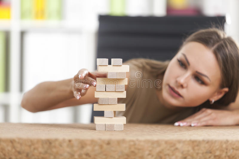 Businesswoman and a wooden tower. Concentrated girl in beige is building a tower from wooden bricks at her workplace in a white office. Concept of a break royalty free stock photos