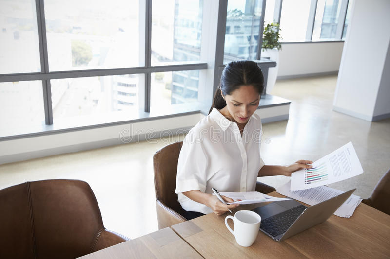 Businesswoman Working Alone On Laptop In Office Boardroom stock image