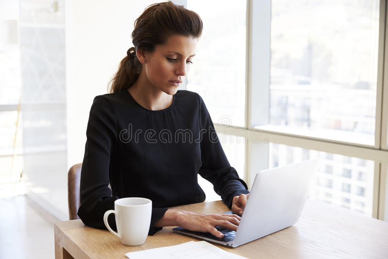 Businesswoman Working Alone On Laptop In Office Boardroom stock photography