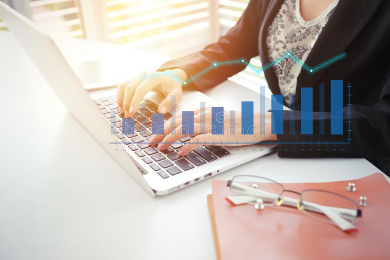Businesswoman working on analytics and reporting company profit summary with laptop computer and glasses on desk royalty free stock images