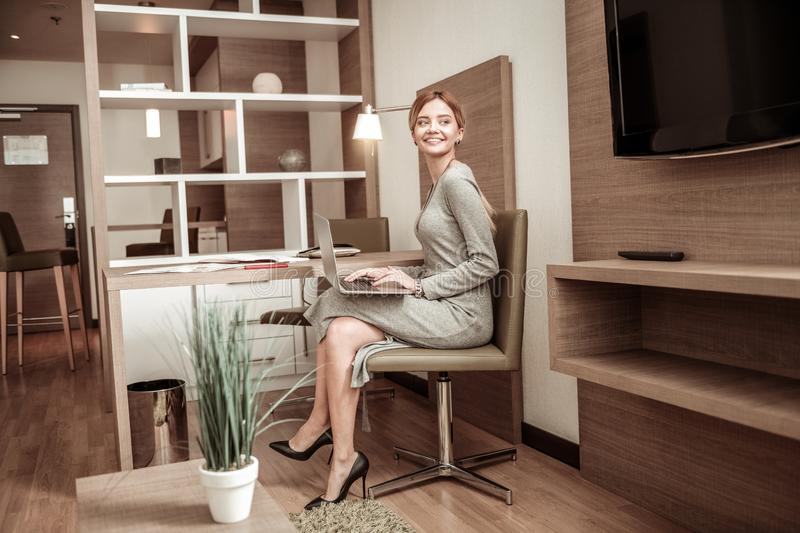Businesswoman working in cozy spacious hotel room. Spacious hotel room. Beaming appealing young businesswoman working in cozy spacious hotel room royalty free stock image