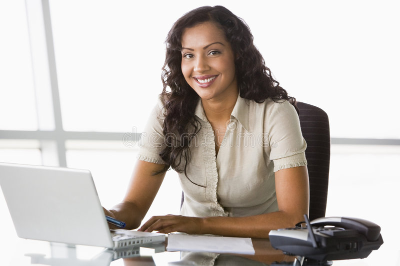 Businesswoman working at desk stock image