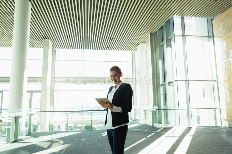 Businesswoman working on digital tablet in a modern office building. Happy businesswoman working on digital tablet in a modern office building. Modern corporate royalty free stock images