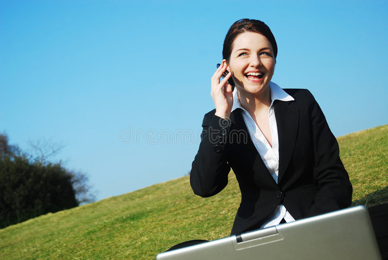 Businesswoman working in field. A beautiful young busiensswoman sitting with her laptop on the phone out in a field with a blue sky stock image