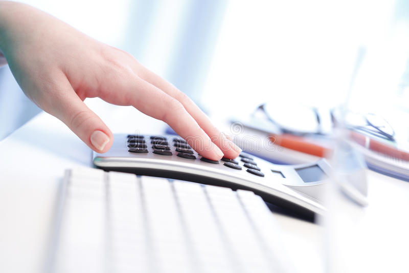 Businesswoman working on financial plan. Close-up of female accountant making calculations while sitting at desk in office stock photo