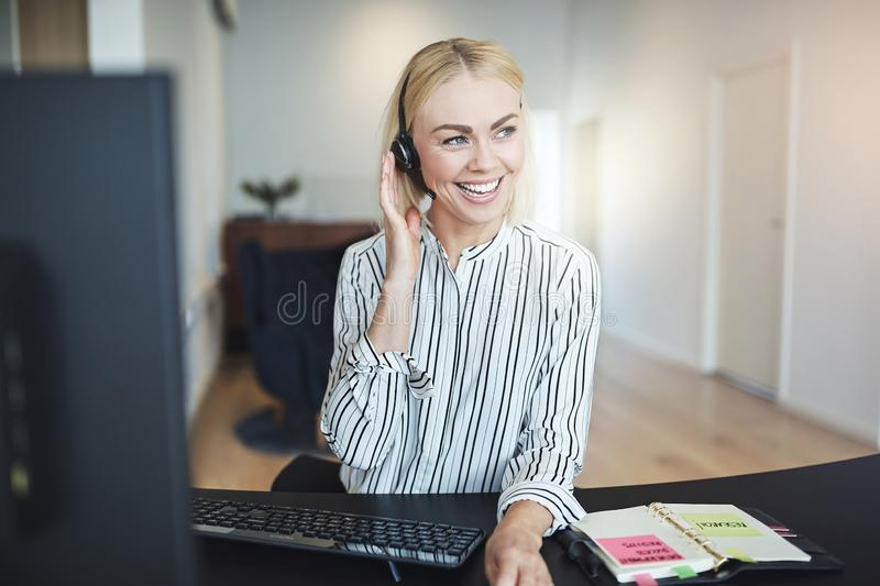 Businesswoman working on her computer and talking on a headset stock photography