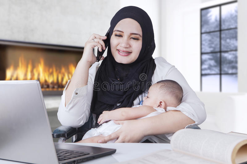 Businesswoman Working while Holding her Baby stock image