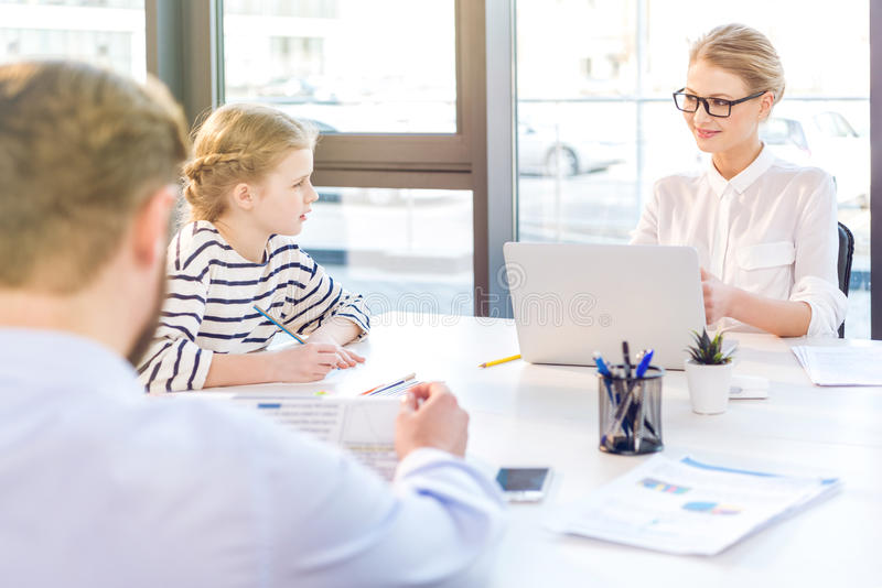 Businesswoman working with laptop, businessman reading newspaper and daughter drawing near royalty free stock images