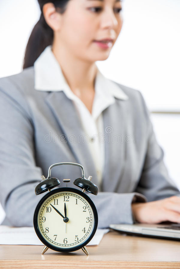 Businesswoman working on laptop with clock showing time. Asian Businesswoman working on laptop with clock showing time royalty free stock photos