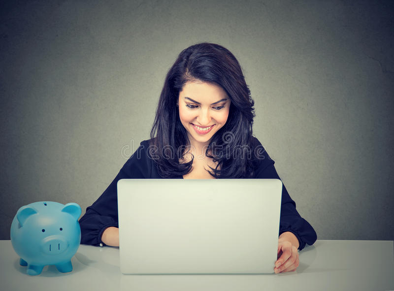 Businesswoman working with laptop computer sitting at desk with piggy bank. Happy businesswoman working with laptop computer sitting at desk with piggy bank royalty free stock images