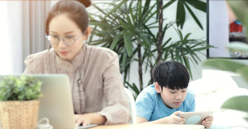 Woman working on laptop with boy playing tablet computer . stock photo