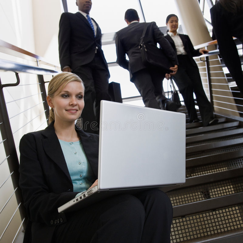 Businesswoman working on laptop on office stairs. Businesswoman sitting and working on laptop on busy office stairs royalty free stock photography