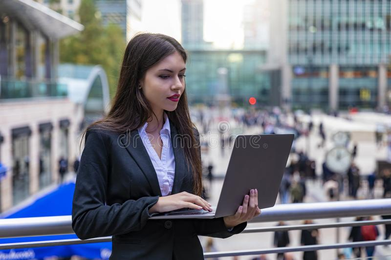 Businesswoman working on a laptop outdoors in the city stock photos