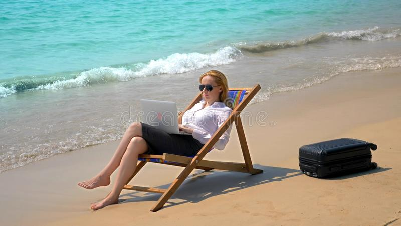 Businesswoman working on a laptop while sitting in a lounger by the sea on a white sandy beach. freelance or workaholism royalty free stock photo