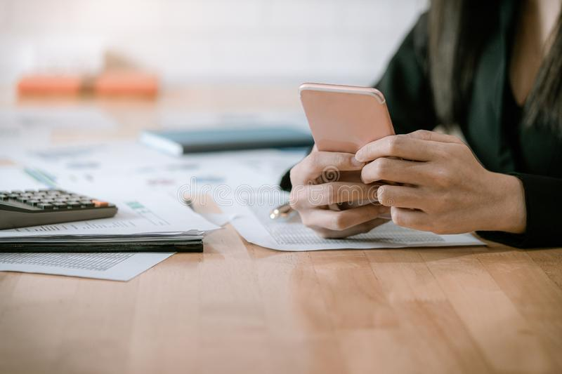 Businesswoman working with a mobile phone above the contract. Business and partnership concept royalty free stock photo