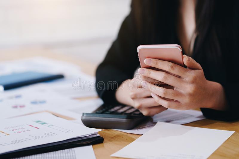 Businesswoman working with a mobile phone above the contract and calculator. Business and partnership concept royalty free stock photos