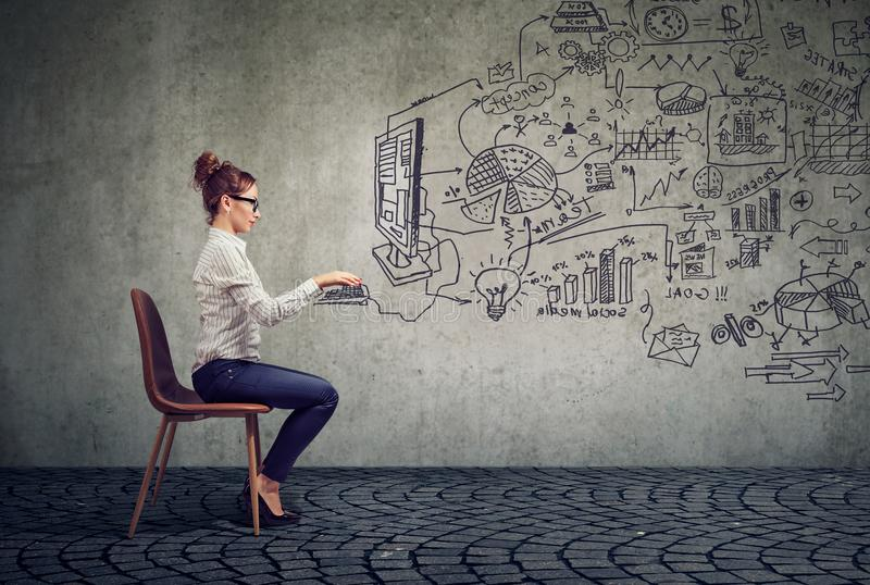 Businesswoman working in an office brainstorming business plan. Young business woman working in an office brainstorming business plan royalty free stock images
