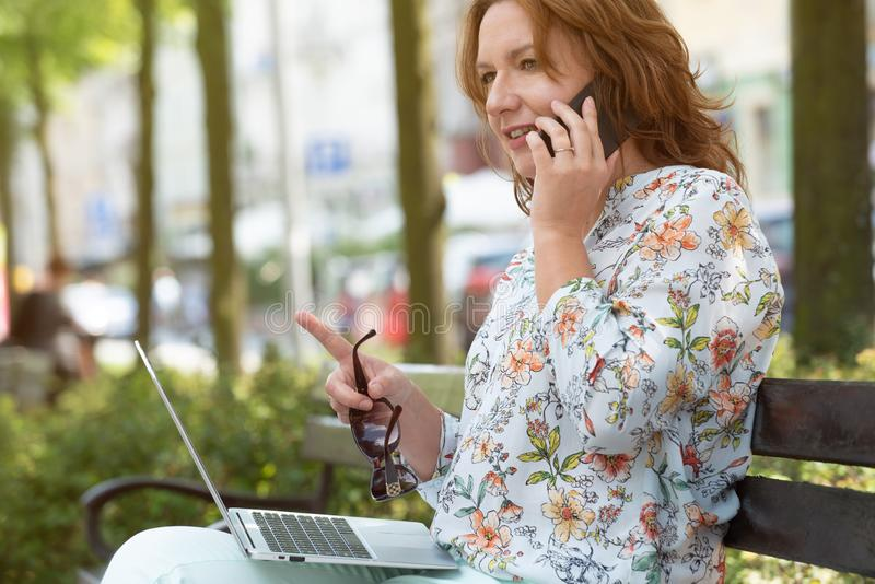 Businesswoman working outdoors with notebook and smart phone royalty free stock photo