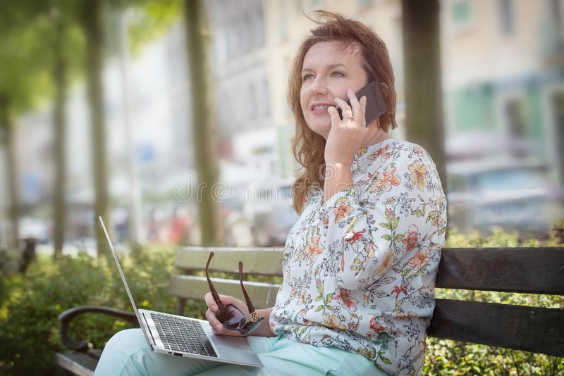 Businesswoman working outdoors with notebook and smart phone stock photo