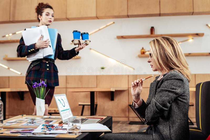 Businesswoman working while secretary bringing her coffee stock photo