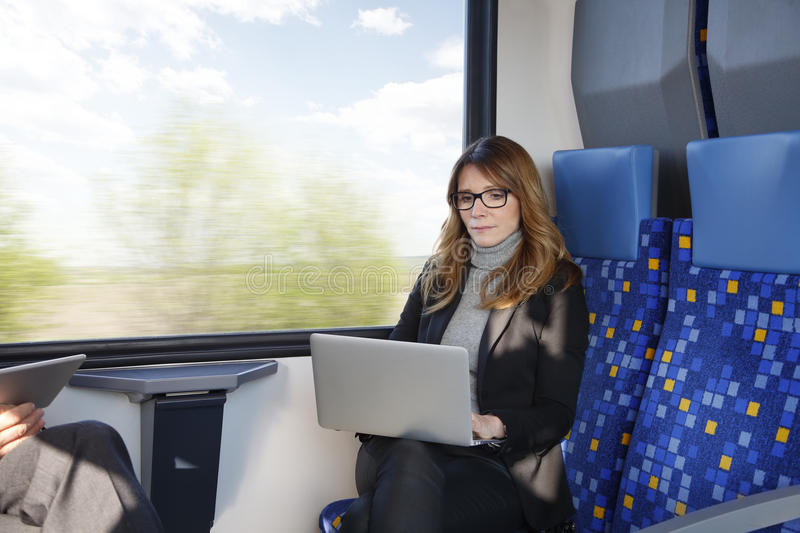 Businesswoman working on train royalty free stock photography
