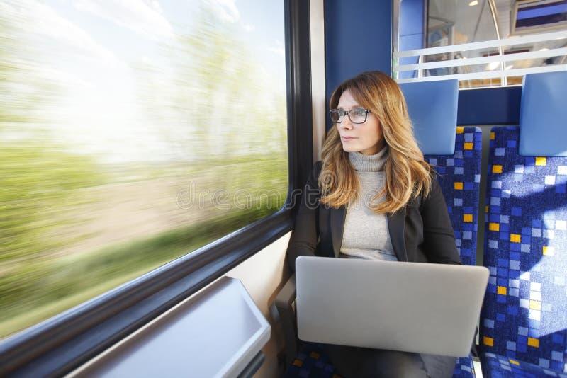 Businesswoman working on train stock image