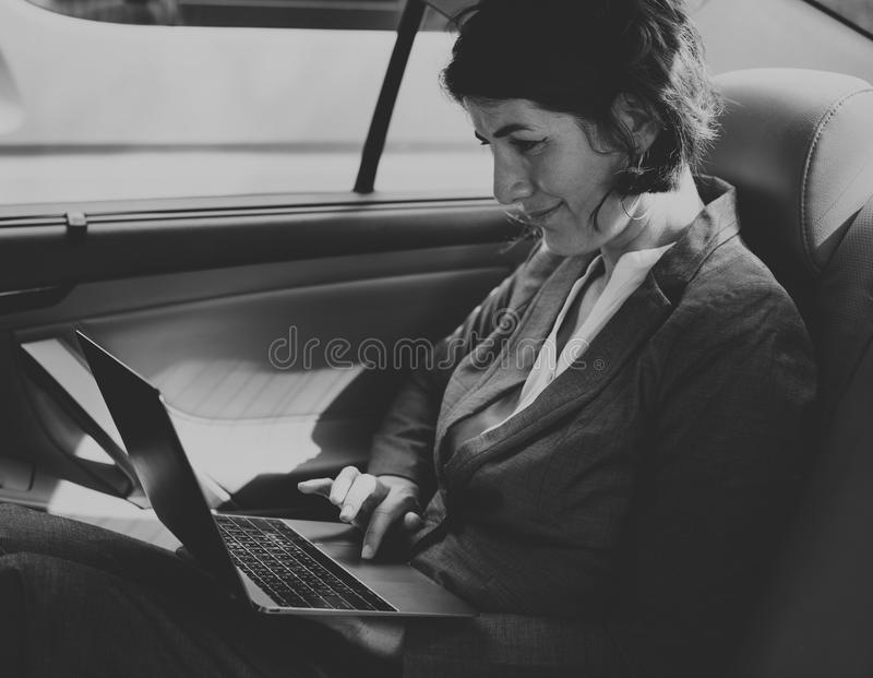 Businesswoman Working Using Laptop Car Inside Concept. Businesswoman Working Using Laptop Car Inside stock image