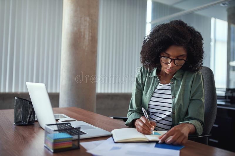Businesswoman writing in an agenda on a desk at office. Close-up of an african young businesswoman writing schedule in diary over the wooden desk in the office stock photo