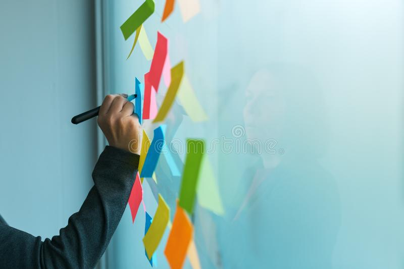 Businesswoman writing on colorful sticky note paper stock image