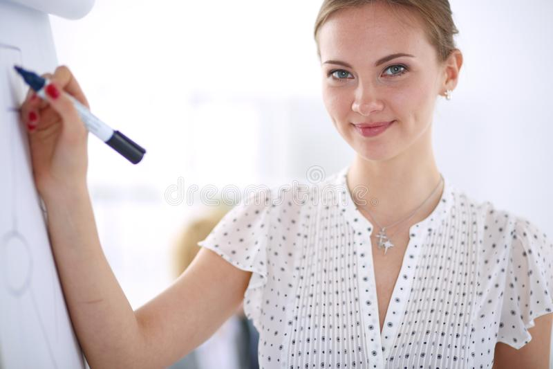 Businesswoman writing on flipchart while giving presentation to colleagues in office . Businesswoman.  royalty free stock photography