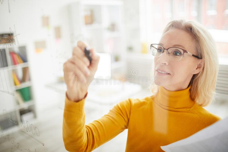 Businesswoman Writing on Glass. High angle portrait of mature businesswoman writing on glass wall in office while planning startup project, copy space stock photo