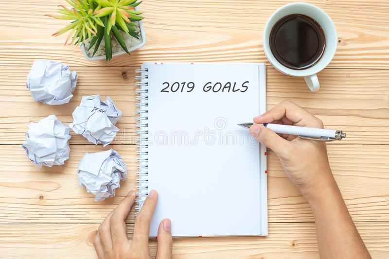 Businesswoman writing 2019 Goals with notebook, crumbled paper and black coffee cup on table. New Year Start, Creative, Idea, Reso stock photo