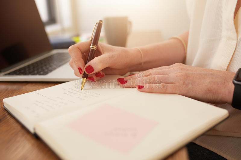 Businesswoman writing in her personal organizer stock image