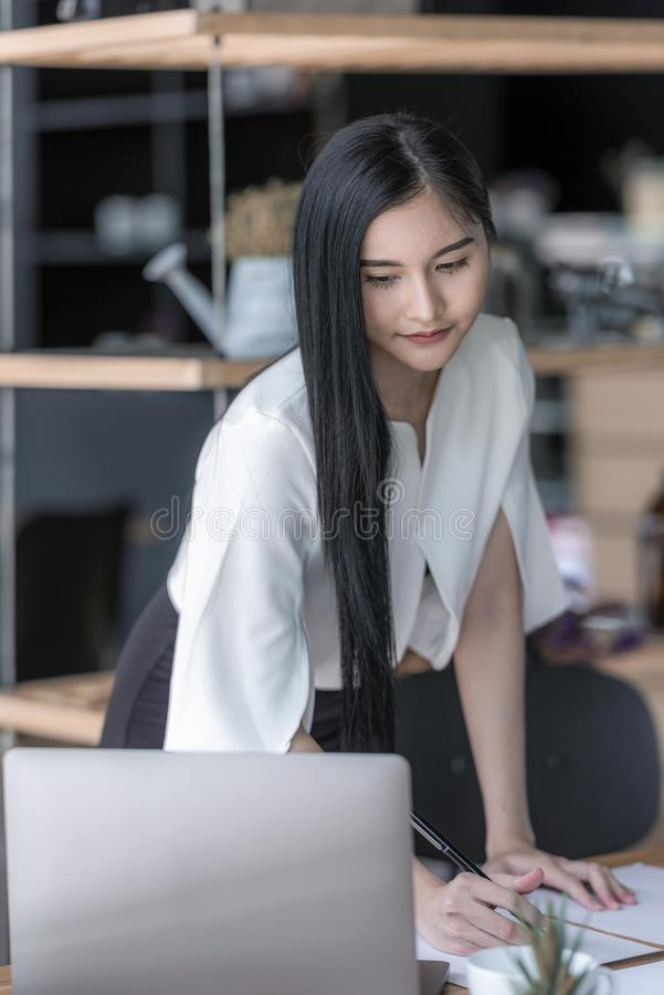 Businesswoman writing while looking at laptop screen royalty free stock photos