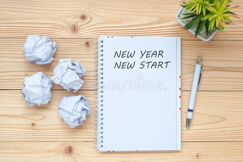Businesswoman writing New Year New Start with notebook, crumbled paper and black coffee cup on table. Creative, Idea, Resolution, royalty free stock image