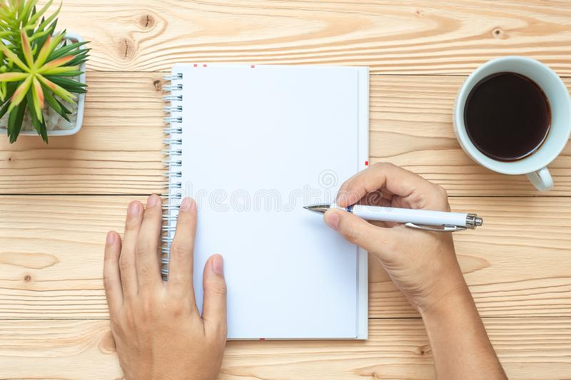 Businesswoman writing with notebook, black coffee cup, pen and glasses on table, Top view and copy space. Goals, Target, Solution, stock photography