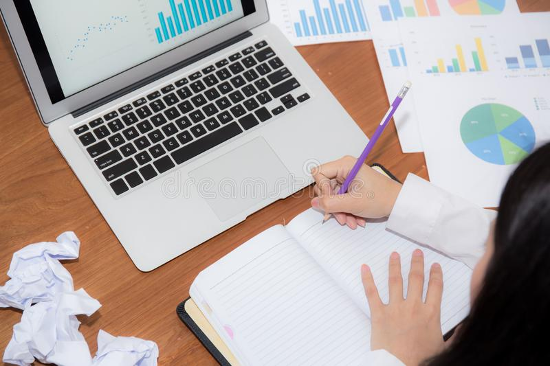 Businesswoman writing on notebook at desk, asian woman with not idea with graph analysis laptop and crumpled paper at office. Businesswoman writing on notebook royalty free stock photo