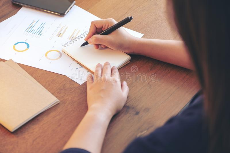 A businesswoman writing on notebook and working on business data and document. On the table in office stock photos