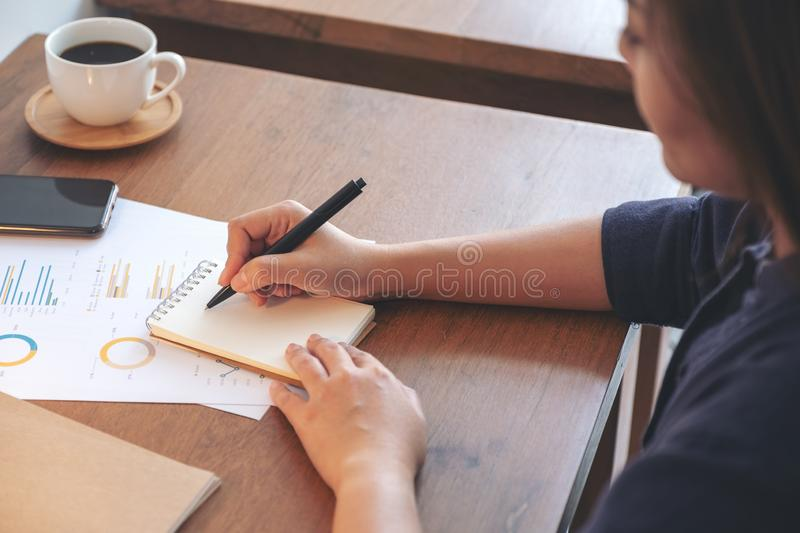 A woman`s hands writing on notebook and working on business data. A businesswoman writing on notebook and working on business data and document on the table in royalty free stock images