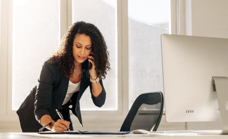 Businesswoman writing notes standing at her desk royalty free stock photography