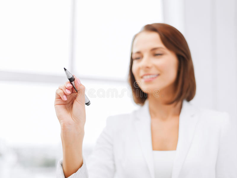 Businesswoman writing something in the air. Office, business, technology concept - businesswoman writing something in the air with marker royalty free stock photography