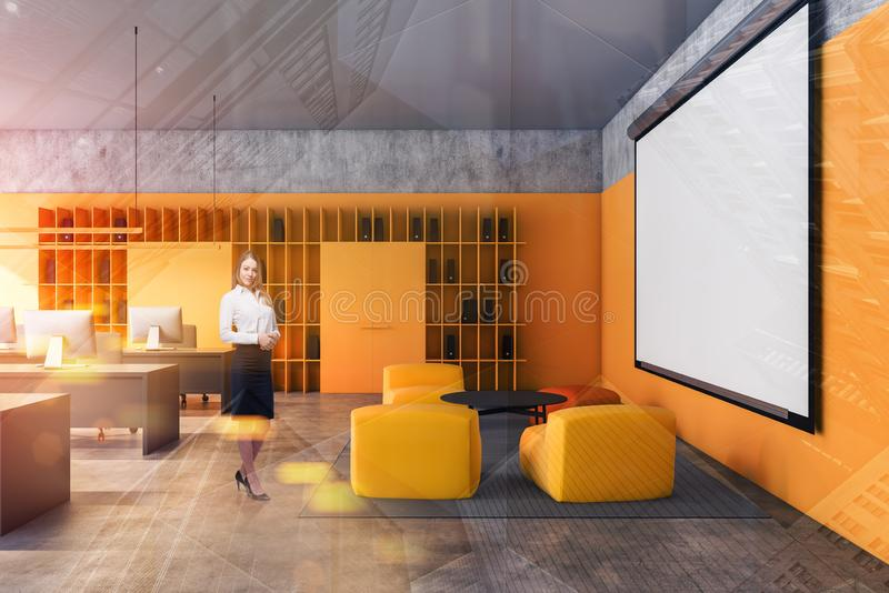 Businesswoman in yellow loft office with screen. Smiling young businesswoman standing in modern loft office with yellow armchairs in lounge area, rows of stock photography